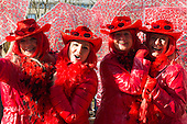Düsseldorf, Germany. 15 February 2015. Four women in red costumes holding umbrellas. Street carnival celebrations take place on Königsallee (Kö) in Düsseldorf ahead of the traditional Shrove Monday parade (Rosenmontagszug).