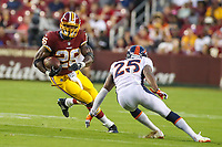 Landover, MD - August 24, 2018: Washington Redskins running back Adrian Peterson (26) runs past Denver Broncos defensive back Chris Harris (25) during the preseason game between Denver Broncos and Washington Redskins at FedEx Field in Landover, MD.   (Photo by Elliott Brown/Media Images International)