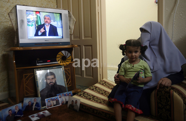 Relatives of Palestinian prisoner Rawhy Mushtaha, held in an Israeli jail, sit in thier house in Gaza City, as they watch a television broadcast of Hamas leader Khaled Meshaal speaking in Damascus, October 11, 2011. Israel and Gaza's Hamas Islamist rulers agreed on Tuesday to swap more than 1,000 Palestinian prisoners for Israeli captive soldier Gilad Shalit, resolving one of the most emotive and intractable issues between them. Photo by Ali Jadallah