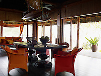 The beach pavilion is furnished with a mahogany drawing table and orange Dedon armchairs
