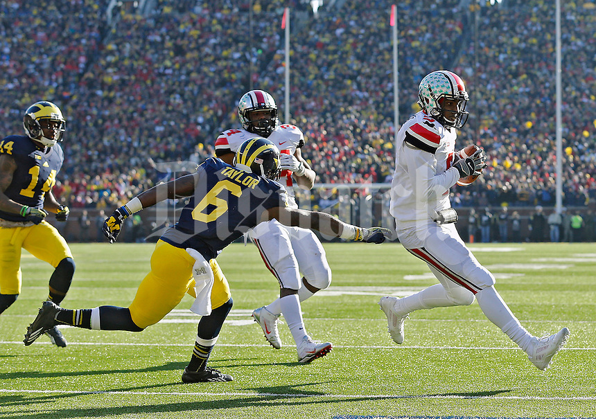 Ohio State Buckeyes quarterback Braxton Miller (5) scores a running touchdown against Michigan Wolverines defensive back Raymon Taylor (6) in the 3rd quarter of their college football game at Michigan Stadium in Ann Arbor, Michigan on November 30, 2013.  (Dispatch photo by Kyle Robertson)