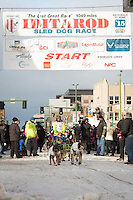 Nicolas Petit and team leave the ceremonial start line with an Iditarider at 4th Avenue and D street in downtown Anchorage, Alaska during the 2015 Iditarod race. Photo by Jim Kohl/IditarodPhotos.com