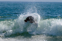 A surfer completes a turn on a breaking wave at Rockaway Beach, NY.