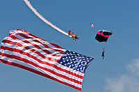 May 28, 2011.     Cindy Irish of the Misty Blues All Women Skydiving Team flies with the American flag during the introductory National Anthem while stunt pilot Gene Soucy circles the flag prior to the start of the St. Augustine Air Show in St. Augustine, Florida.