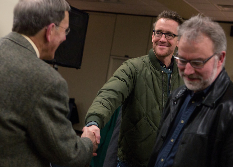 Tom Carpenter, left, the 2013 recipient of Ohio University's Distinguished Professor Award, shakes hands with Geoff Buckley, right, after the Distinguished Professor Lecture and award reception in Alden Library on Feb. 24, 2014. Photo by Lauren Pond