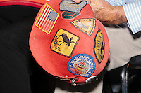 A man holds a hat with New Hampshire and other New England patches while Vermont senator and Democratic presidential candidate Bernie Sanders speaks at a campaign event at the White Mountain Chalet event hall in Berlin, New Hampshire.