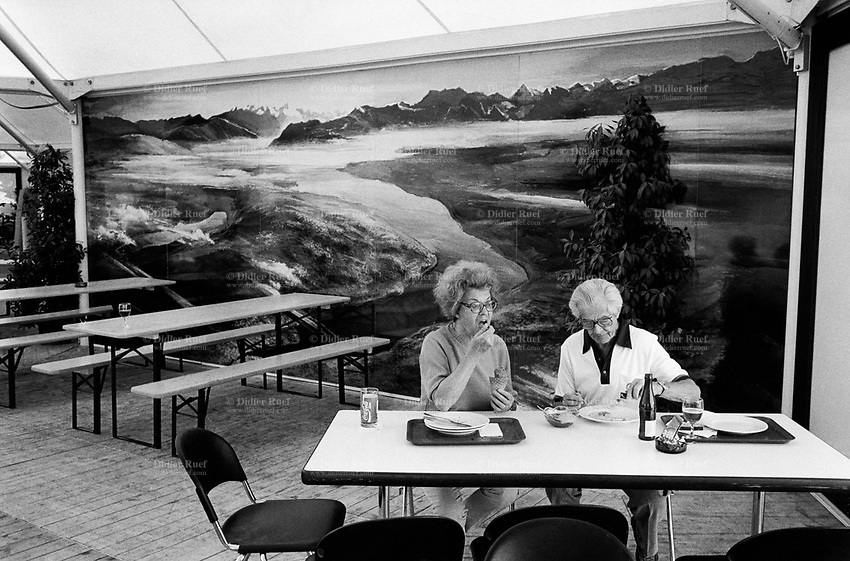Switzerland. Zürich. An old couple is enjoying a meal together. A picture of an alpine scenery is on the wall. Swiss Alps.   © 1990 Didier Ruef