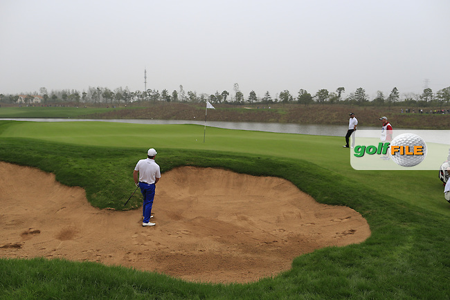 Graeme McDowell (NIR) chips from a bunker at the 17th green during Saturay's Round 3 of the 2014 BMW Masters held at Lake Malaren, Shanghai, China. 1st November 2014.<br /> Picture: Eoin Clarke www.golffile.ie