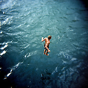 The boy jumps from landing stage in the black sea. Abkhazia. Gagra town. 2009