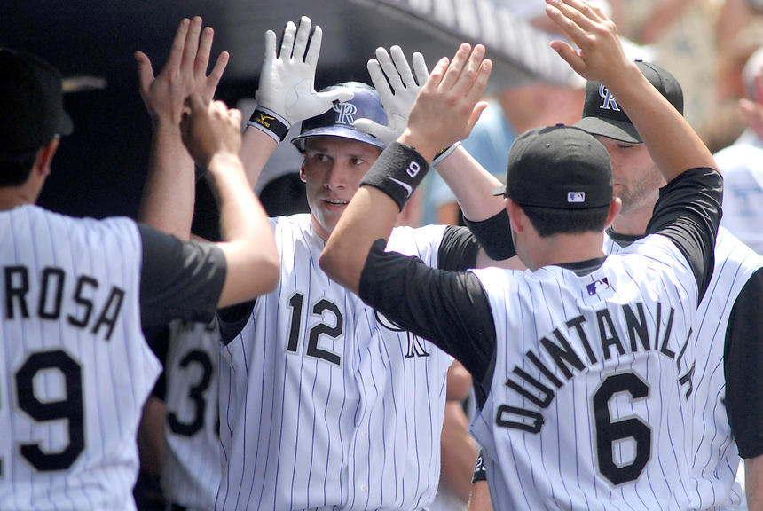 20 July 08: Colorado Rockies shortstop Clint Barmes (12) is congratulated by teammates after scoring a run against the Pittsburgh Pirates. The Rockies defeated the Pirates 11-3 at Coors Field in Denver, Colorado.