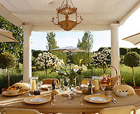 A table laid for lunch beneath a shady porch looks out onto a well-kept garden