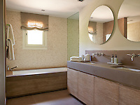 In this bathroom the warm tones of the natural linen Roman blind combine with the limed woodwork of the bath and cupboards