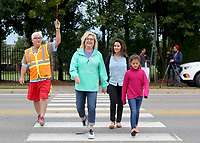NWA Democrat-Gazette/DAVID GOTTSCHALK Dale Duerr (from left), physical education teacher at Walker Elementary School, helps Wednesday, October 10, 2018, monitor the crosswalk as Mary Miller walks with Sarah Jones and her daughter Sophia, a third grade student at the school in Springdale. Walker Elementary School participated in National Walk to School Day. Studies have shown that walking to school positively influences academic achievement, student morning energy levels, attention, truancy, and absenteeism.