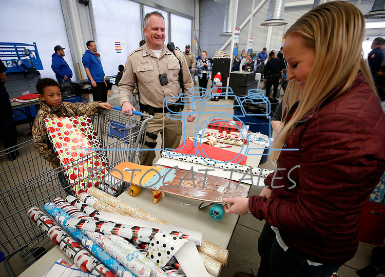 Douglas County Sheriff's Deputy Joe Duffy talks with Lisa Holland, from Hometown Health, as she wraps a skateboard for Ellijah, 8, during the 15th annual Holiday with a Hero program at Walmart in Carson City, on Wednesday, Dec. 19, 2018. The program, which pairs local heroes with more than 200 K-8th graders, provides a $100 Christmas shopping spree at Walmart.  <br /> Photo by Cathleen Allison/Nevada Momentum