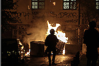 Pictured: A riot police officer's silhouette against burning wheelie bins in Exarchia, central Athens Tuesday 02 December 2014<br />