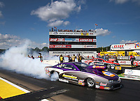Aug 15, 2014; Brainerd, MN, USA; NHRA pro stock driver Vincent Nobile (near lane) burns out alongside V. Gaines during qualifying for the Lucas Oil Nationals at Brainerd International Raceway. Mandatory Credit: Mark J. Rebilas-
