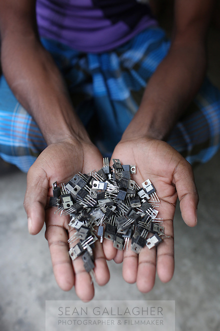 A man holds recycled electronics in his hands in the village of Sangrampur, located south of Kolkata in northeast India. Globally, an estimated 50 million tons of e-waste are produced annually, and much of it ends up in countries like India. November, 2013