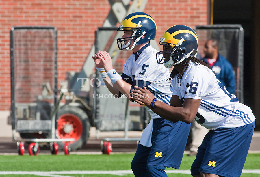 Michigan quarterbacks Tate Forcier (5) and Denard Robinson (16) participating in a drill on the first day of spring football practices, Tuesday, March 16, 2010, in Ann Arbor, Mich. (AP Photo/Tony Ding)