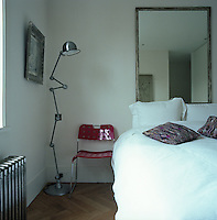 An antique angle-poise floor lamp is placed next to the guest room bed while a red plastic retro chair serves as a bedside table