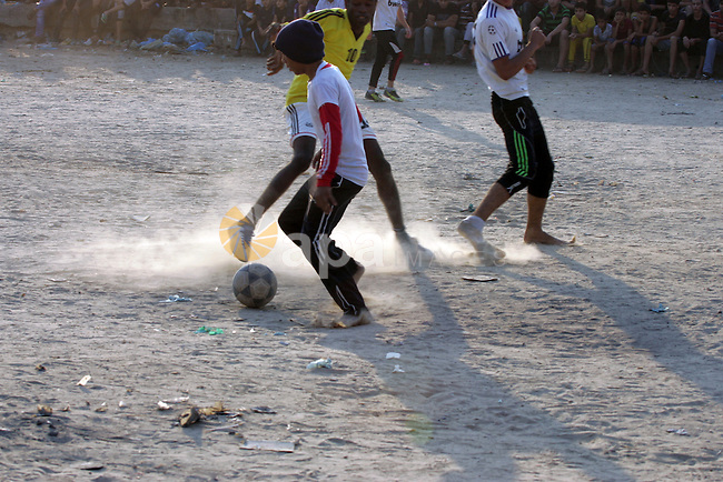 Palestinian youths play football match, at a refugee camp in Rafah, in the southern Gaza Strip, during the Muslim holy month of Ramadan on June 28, 2015. Muslims around the world abstain from food, drink and sexual intercourse from sunrise to sunset during Ramadan. Photo by Abed Rahim Khatib
