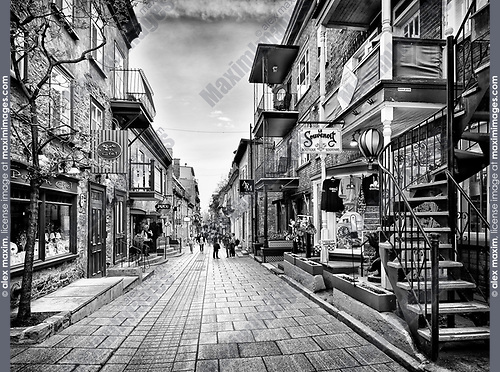 Rue du Petit Champlain in old Quebec City with its colorful shop windows and restaurants. Pot en Ciel, le Souvenoit and other stores, Quebec, Canada. Black and white photo. Ville de Québec.