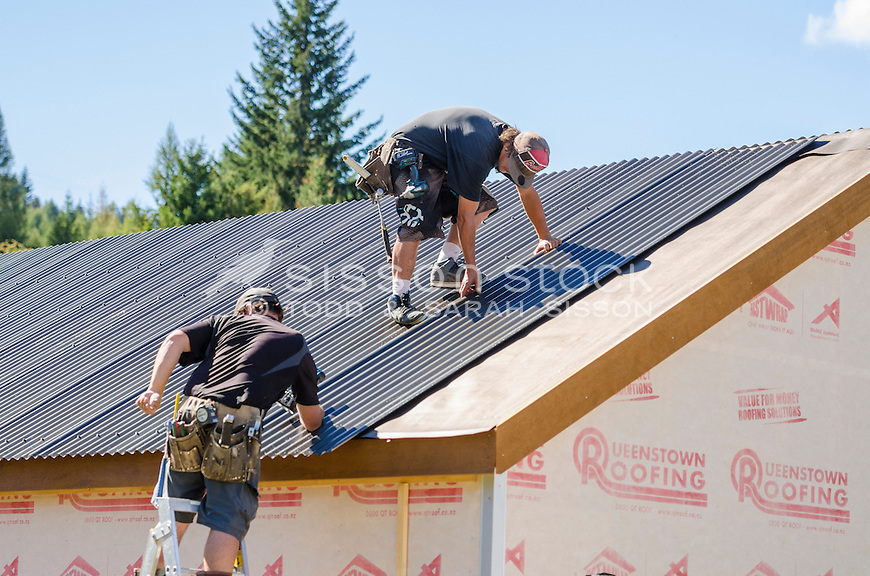 Roofers applying corrugate sheets to a new house, Queenstown, New Zealand - stock photo, canvas, fine art print