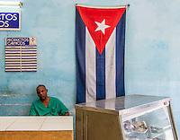 HAVANA, CUBA, 22.07.2015 –  Comerciante ao lado da bandeira de Cuba em um comercio no bairro Habana Vieja.(Foto: Paulo Lisboa/Brazil Photo Press)