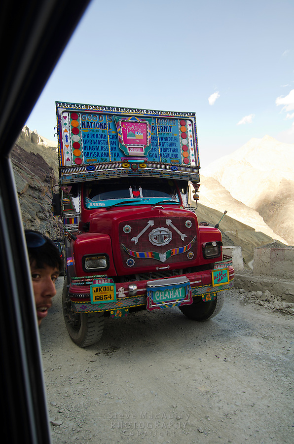A close call as a large, colorfully decorated transport truck passes on a narrow stretch of the Srinagar to Leh road, Ladakh, India.