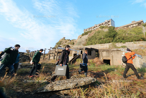 """In this December 11, 2013 photo, director Shinji Higuchi ゥ carries equipments along with his staffs during a location hunting for his film, """"Attack on Titan"""" on Hashima Island, commonly known as Gunkanjima, which means """"Battleship Island"""" off Nagasaki, Nagasaki Prefecture, southern Japan. (Photo by Yuriko Nakao/AFLO) (No Third Party Sales, Minimum $50.00 Per Image)"""
