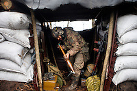 "UKRAINE, 02.2016, Oblast Donetsk. Ukrainian-Russian conflict concerning Eastern Ukraine / Foreign volunteers (""Task Force Pluto"") fighting with the far-right militia Pravyi Sektor against the Russian-backed separatists: Ben (Austria) assembles RPG-7 rocket propelled grenade parts in a trench shelter at the Donetsk frontline. © Timo Vogt/EST&OST"