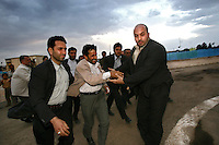 Iranian President Mahmoud Ahmadinejad's bodyguards guide the diminutive leader towards his helicopter after a speech delivered in the city of Arak.