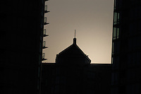 The silhouette of appartment condos and a tower at dawn