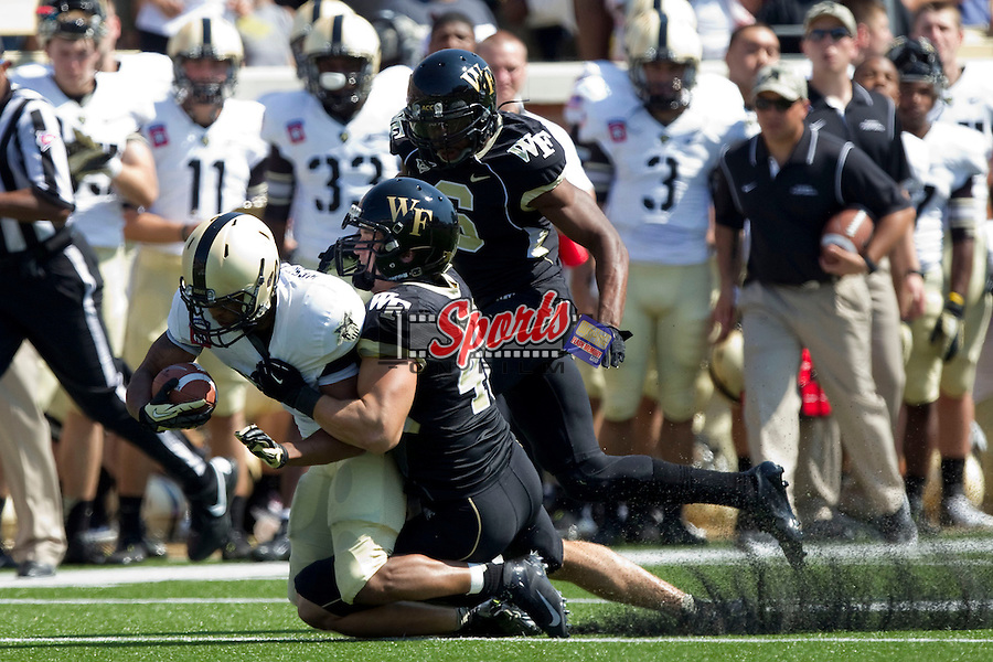 Malcolm Brown (23) of the Army Black Knights is dragged down from behind by Joey Ehrmann (40) of the Wake Forest Demon Deacons at BB&T Field on September 22, 2012 in Winston-Salem, North Carolina.  The Demon Deacons defeated the Black Knights 49-37.  (Brian Westerholt/Sports On Film)