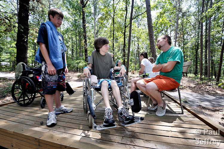 Campers Scuyler Dusty (left) and Brandon Goodwin (in wheelchair) share with counselor Jimmie Ray DuVall at Camp Aldersgate in Little Rock, Arkansas. The camp, supported by United Methodist Women, offers children suffering from a variety of disabilities a safe and fun experience similar to that which normally-abled children often enjoy.