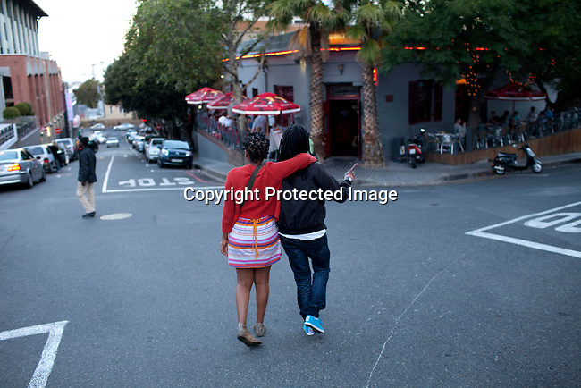 CAPE TOWN, SOUTH AFRICA - DECEMBER 16: Natasha Mbisi and her girlfriend Zama Shange walks in the Cape Quarter gay area on December 16, 2011 in Cape Town, South Africa. Cape Town is a city known for tolerating gays and lesbians except in the townships where they get harassed and often attacked. Some women have been raped in so called corrective rape, where men rapes them to make them women again. They can't show their love freely on the streets in the townships so they usually have to meet in houses and this bar. In central Cape Town, there's many bars and restaurants for gays and lesbians. (Photo by Per-Anders Pettersson)