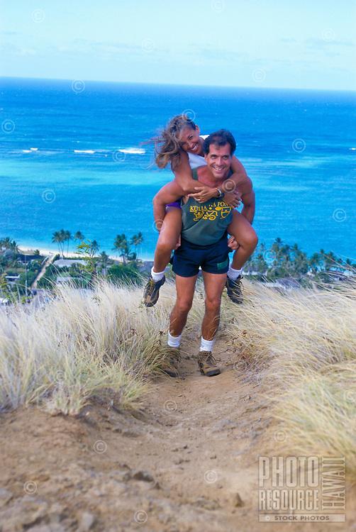 Couple playing on a hiking trail, Lanikai ridge, Oahu