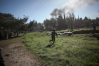 Syrian rebel fighters run for cover as they sneak through enemy's fire during heavy clashes at Madrasat Al-Mushaat, one militar academy besieged by rebels at the north of Aleppo, Syria.