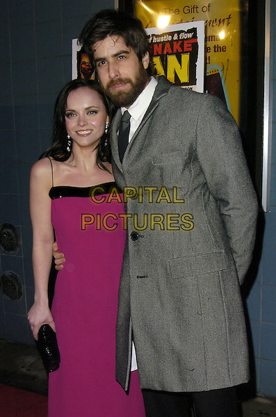 "CHRISTINA RICCI & ADAM GOLDBERG.Premiere of ""Black Snake Moan"" at the Chelsea West Cinemas, New York, New York, USA..February 19th, 2007.half length fuschia pink purple dress black clutch purse grey gray coat beard facial hair .CAP/ADM/BL.©Bill Lyons/AdMedia/Capital Pictures *** Local Caption ***"