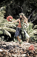 Young hula dancer in ti leaf skirt at Hawaiian heiau (temple site) dancing with uliuli (feathered gourd rattles)