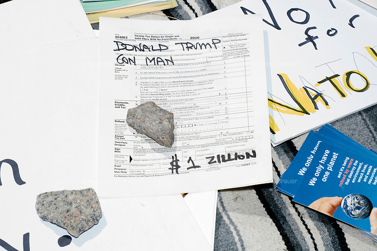 Anti-Trump signs lay on the ground in Cambridge Common during a Tax Day protest near Harvard Square in Cambridge, Mass., on Sat., April 15, 2017. The demonstrators called for President Donald Trump to release his tax returns. Trump refused to release his tax returns during the 2016 presidential campaign, in contrast to all previous major party presidential candidates, and continues to refuse to release them. The protest was part of a larger movement nationwide called Tax March.