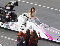 Feb 7, 2015; Pomona, CA, USA; NHRA top alcohol dragster driver Ashley Sanford waves at a group of young girls during qualifying for the Winternationals at Auto Club Raceway at Pomona. Mandatory Credit: Mark J. Rebilas-USA TODAY Sports