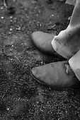 Juruena, Mato Grosso, Brazil. A settler man's feet wearing leather boots, one of which has been cut by a chainsaw, with the man's foot showing the resulting scar, standing on charred ground.