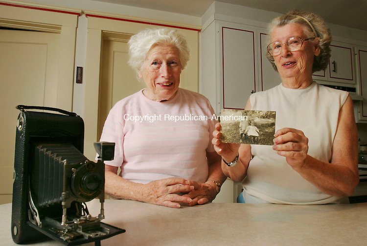 TORRINGTON,  CT 26 September 2005 -092605BZ07-  Postcard collectors Hazel Wadhams, left, and her sister Sylvia Wadhams, display a postcard, with a photograph of two of their brothers on it, they found in a batch of Torrington postcards a fellow collector had recently.  The card, featuring a picture of James Gordon Wadhams at age 4 and Arthur Charles Wadhams at age 2 was originally sent by their mother in 1913. The Kodak camera in the foreground was the one used to take the original photograph they said.<br /> Jamison C. Bazinet / Republican-American