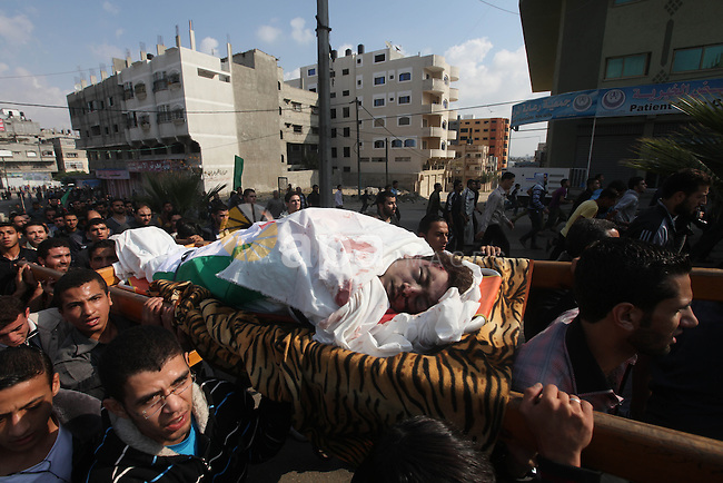 Palestinians carry the bodies of the al-Dallu family during their funeral in Gaza City, 19 November 2012. Nine members of the al-Dallu family died when Israeli forced hit their building in Gaza City one day ago. Media reports state that Israeli forces were on Monday targeting the Palestinian homes and other buildings in its bombardment of the Gaza Strip, as the combined death toll in six days of airstrikes and rocket attacks climbed to nearly 100. Photo by Majdi Fathi