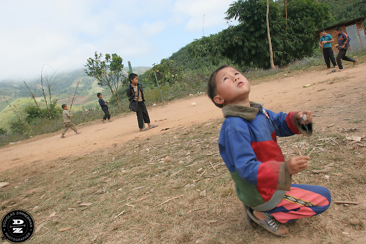 A young child plays with a sling in the village of Ban Kok Mee in the county of Louang Namtha,  Laos.  The multi-ethnic village has the ethnic groups including the Sida, Phounoi, Hmong, and Khmu. Photograph by Douglas ZImmerman