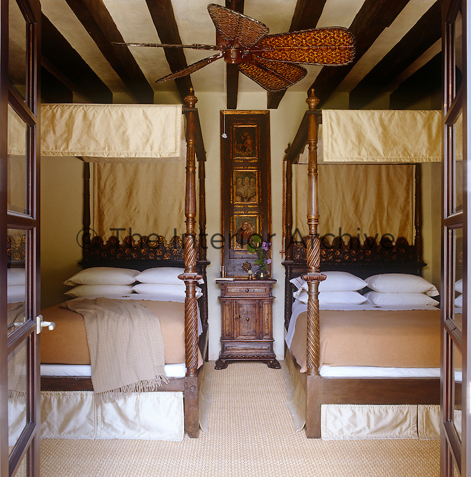 Guatemalan antique four-poster twin beds draped in silk flank an antique screen panel in this guest bedroom