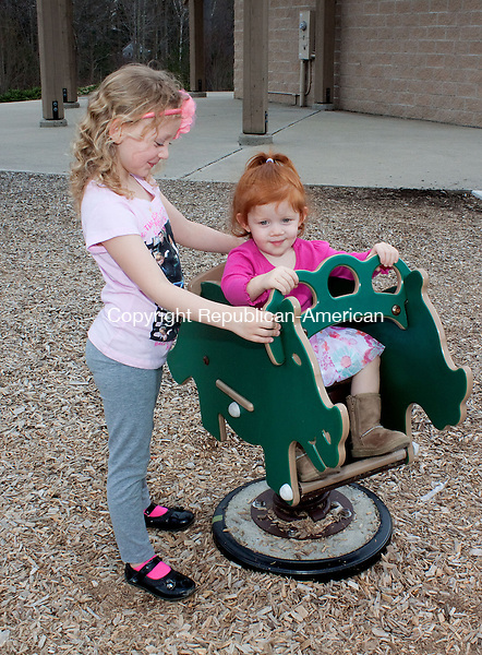 MIDDLEBURY CT-APRIL 10 NEW_0104DA01- Jovi Messina, 4, left, rocks her sister Emilyn, 2, of Naugatuck as they enjoy the warm weather playing at Meadowview Park in Middlebury with their mom on Wednesday..Darlene Douty Republican American