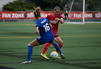 Seattle, WA - Saturday, May 14, 2016: Portland Thorns FC defender Katherine Reynolds (2) tries to dribble the ball around Seattle Reign FC defender Carson Pickett (16) during first half. The Portland Thorns FC and the Seattle Reign FC played to a 1-1 tie during a regular season National Women's Soccer League (NWSL) match at Memorial Stadium.
