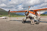 Danielle Terrel and Dirk Nickish fuel Coyote Air De Havilland Beaver airplane, Coldfoot airport, Coldfoot, Alaska.