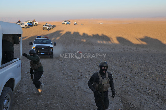 KIRKUK, IRAQ: Iraqi policemen drive to a suspected terrorist training camp during an anti-terror raid..After receiving intelligence about a terrorist training camp in the Hamria mountains, the Kirkuk Regional Police conduct a dawn raid...This is the first anti-terror raid in Kirkuk after the withdrawal of US troops...Photo by Pazhar Mohammad/Metrography